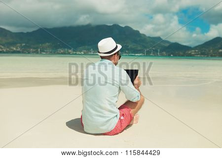 man sitting in the sand with legs crossed while reading from ipad in an exotic place