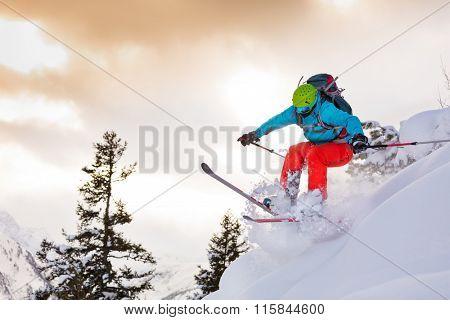 Man freerideer running downhill in forest