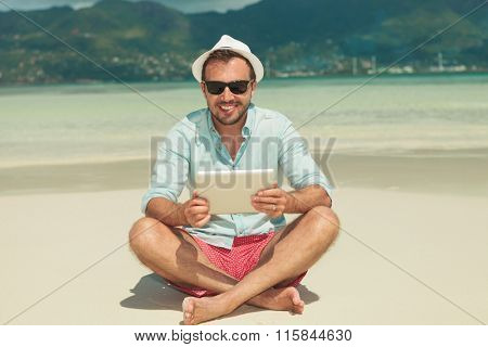 happy young man on the beach holding ipad while sittings legs crossed wearing sunglasses and hat