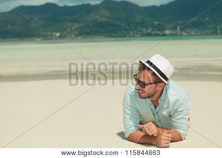 sexy young man laying down in sand on the beach looking away from the camera