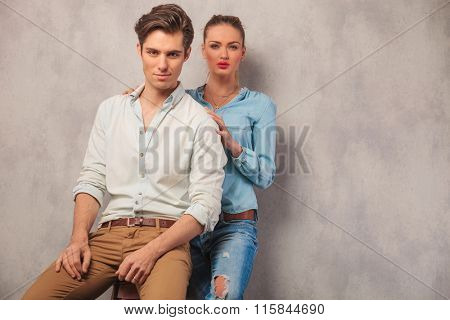 portrait of couple posing in studio, him seated and her in the background standing embracing him