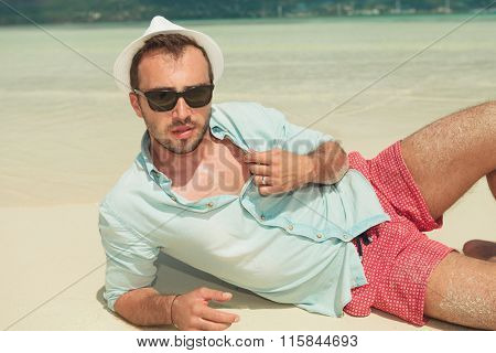 handsome man lying down the beach with white hat and sunglasses on while opening his shirt