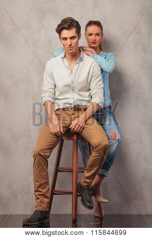 man posing in studio seated while girl in the back rests her hands on his shoulders