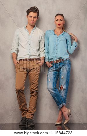 casual couple standing in studio leaning on the wall while posing with hands in pockets