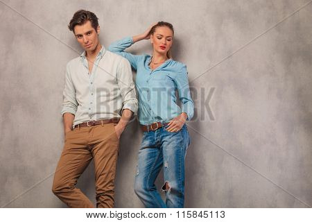handsome man pose in studio background with hands in pockets while woman is resting her arm on his shoulder while posing with hand in pocket