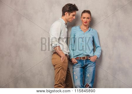 casual couple pose in studio background with hands in pockets, man stares away while the girl is looking at the camera