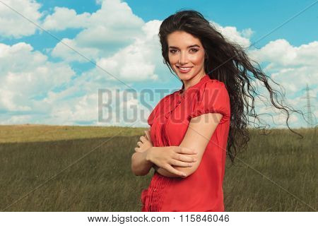 girl with hands crossed smiling in the fields while wind blowing through her hair