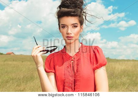 portrait of young woman in the fields, taking off her sunglasses while while looking at the camera