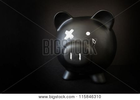 Black piggy bank with a tear and X'd out eye,  taking a beating