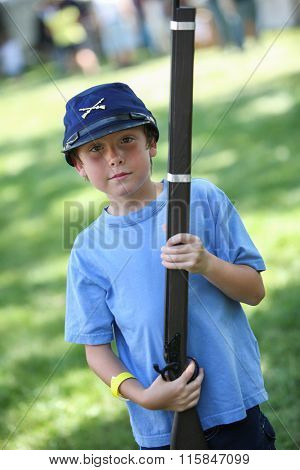 Boy at a Civil War reenactment wearing a union soldier hat and holding a toy musket