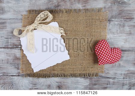 Valentine Day vintage rustic background with ragged paper sheet and red heart