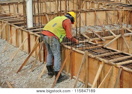 Group of construction workers fabricating ground beam form work