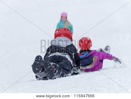 Kids Wearing Helmets Playing In A Snowy Slope