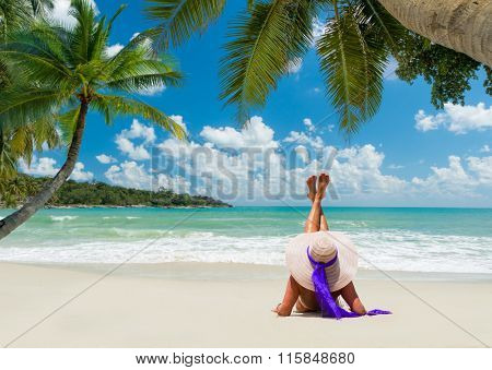young woman in white swimsuit on the beach under the coconut tree