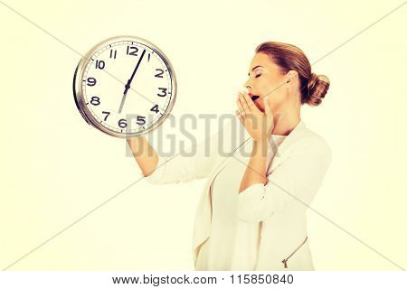 Yawning businesswoman with a clock