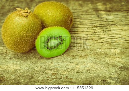 Close Up Slice Of Fresh Kiwi Fruit On Old Wood Background.