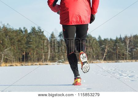 Back view of running sportsman during cross country race outdoor in winter forest
