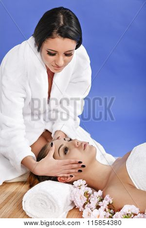 Beautiful  woman in spa salon getting massage, on blue background