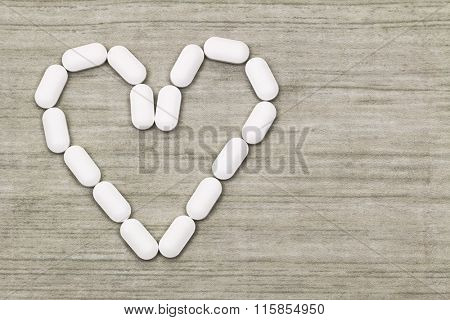 Top view of white tablets in a heart shaped symbol with copyspace
