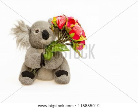 Koala Doll Hold Bouquet Of Red Roses On White Background