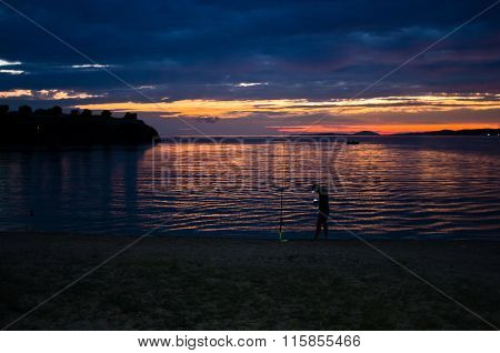 Fisherman at twilight in Toroni bay near old roman fortress, Sithonia