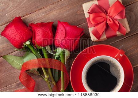 Red roses, Valentines day gift box and coffee cup on wooden background. Top view