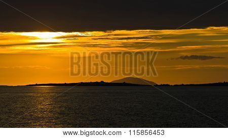 Sunset at sea, with small greek islands in background