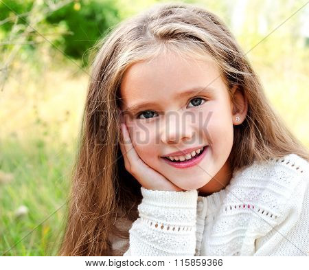 Portrait Of Smiling Cute Little Girl In Summer Day