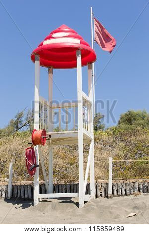 Lifeguard tower with red roof and flag at sandy beach