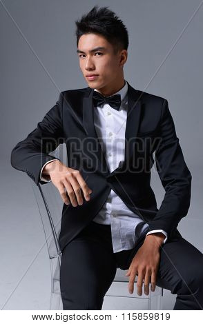 portrait of young business man sitting chair â??gray background