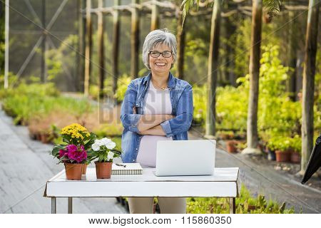 Beautiful mature woman working in a greenhouse, looking at camera and smiling