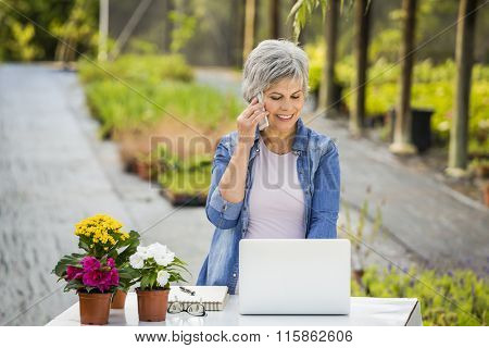 Beautiful mature woman working in a greenhouse and making a phone call