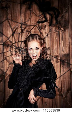 Portrait of a scaring witch lady in black dress. Halloween concept.
