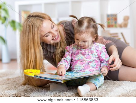 mother reads a book to kid at home
