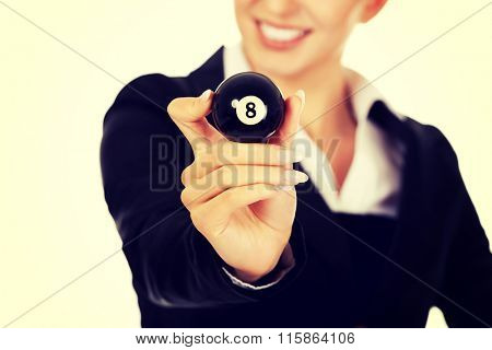 Happy businesswoman holding eight billiard ball.