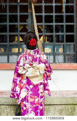 The back view of Japanese Woman pull the rope to ring the bell at temple