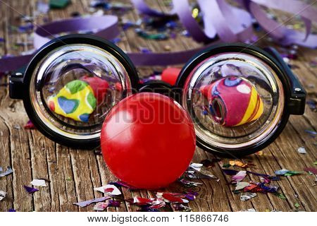 a pair of fake short-sighted eyeglasses and a red clown nose, on a rustic wooden surface full of confetti, party horns and streamers