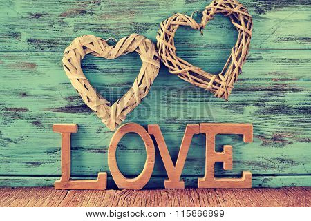 two heart-shaped ornaments made with natural fibers and some wooden letters forming the word love, against a blue rustic wooden background
