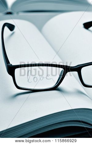 the word love handwritten in a notebook seen through the lens of a black plastic-rimmed eyeglasses, in duotone