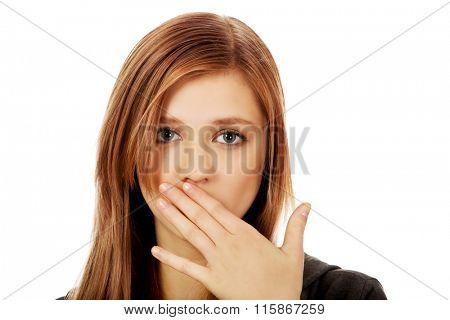 Teenage woman covering mouth with hand