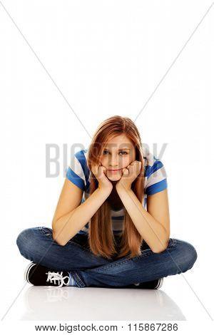 Smiling teenage woman sitting on a floor with legs crossed