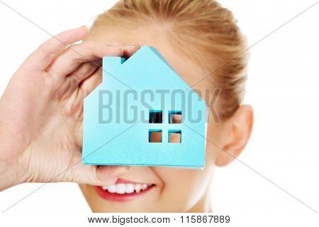 Smile business woman looking through a paper house window