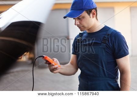 Mechanic using an electronic tester on a car engine