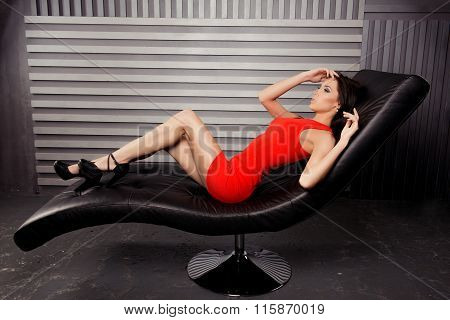 Seductive Brunette Lying On Leather Chair In Red Dress And High Heel Shoes
