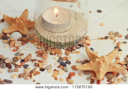 Tea light candle in jar with sea sand.