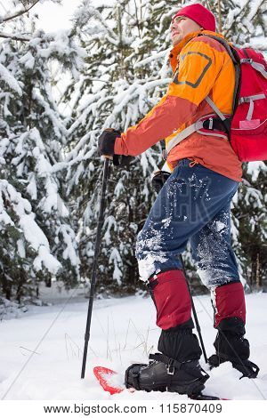 Man walking in snowshoes through the woods with a backpack.