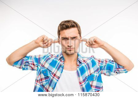 Cute Young Man Closing Ears And Frowning