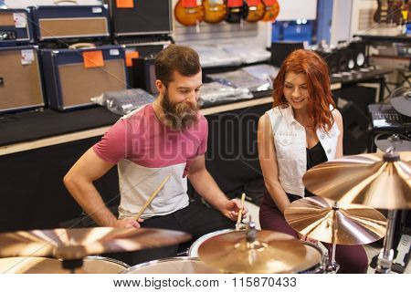happy man and woman playing cymbals at music store