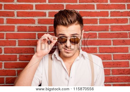 Serious Young Man With Grimace On Face Touching His Spectacles