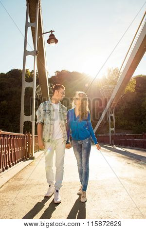Cheerful Nice Couple In Love On The Bridge Walking Together